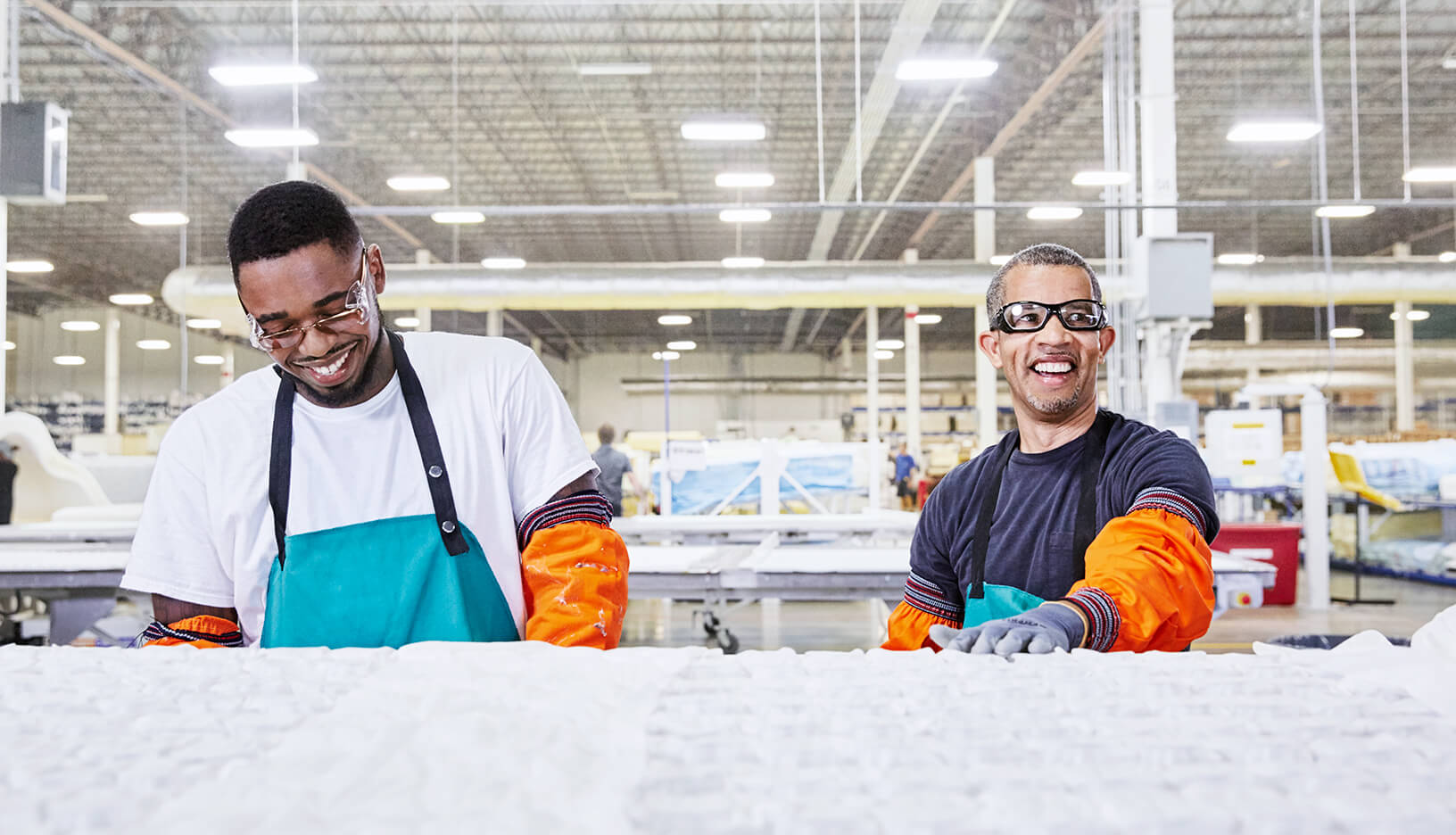 Two men smiling at work in a manufacturing plant