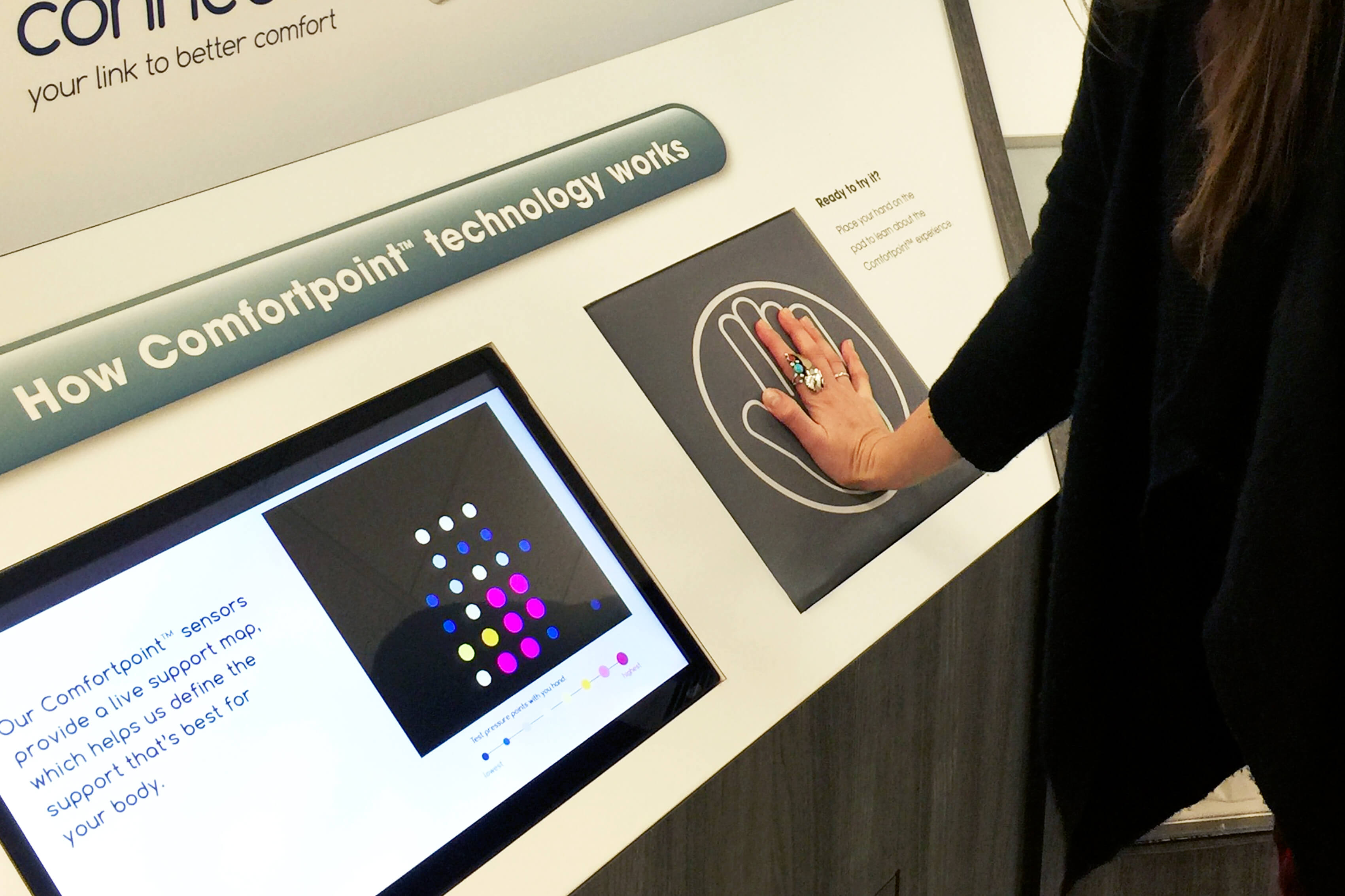 Image of woman's hand on interactive screen